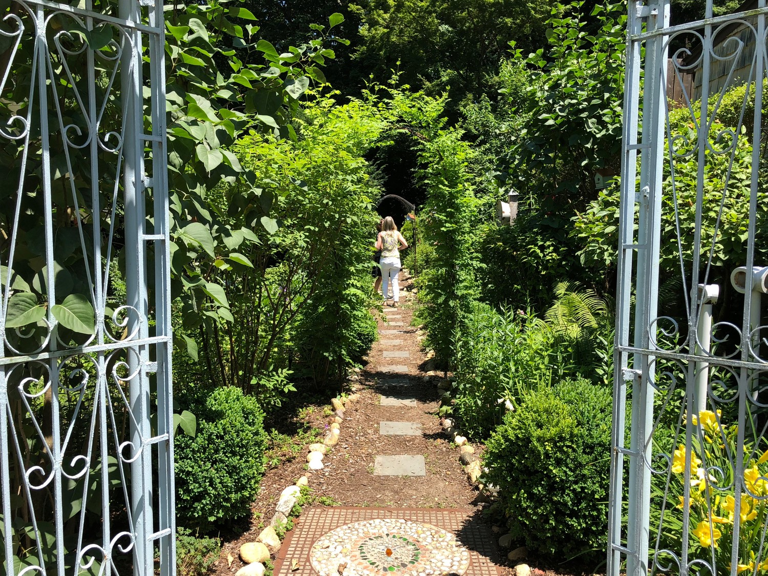 Visitors to Posey Heisig's French-inspired gardens were enveloped in a sea of green as they entered the backyard. She has been designing gardens for 30 years.