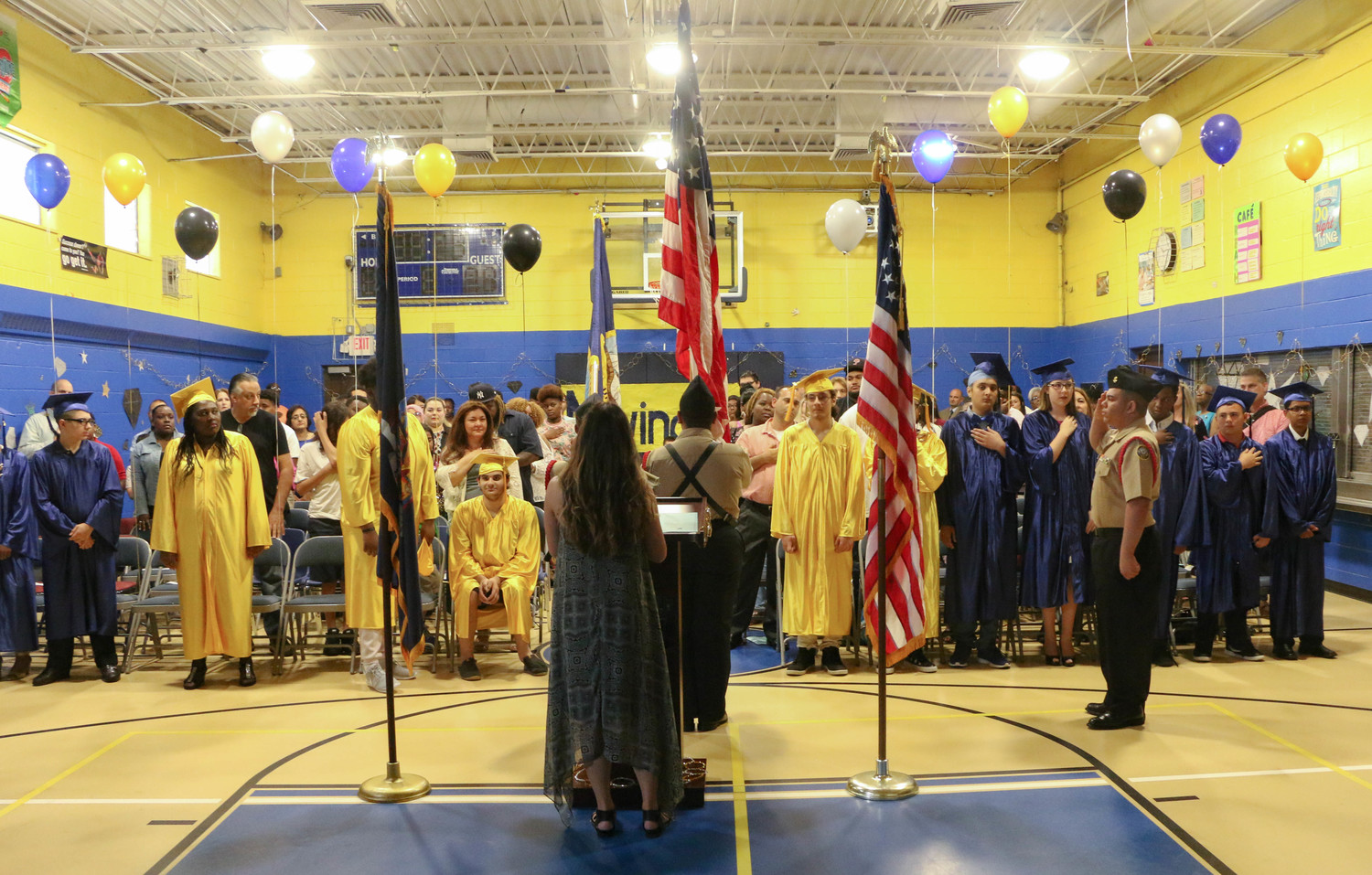 Freeport High School NAVY ROTC Color Guard, saluted the flag while Christina Cuevas, center, led graduates and attendees in the singing of the Star Spangled Banner during the graduation ceremony.