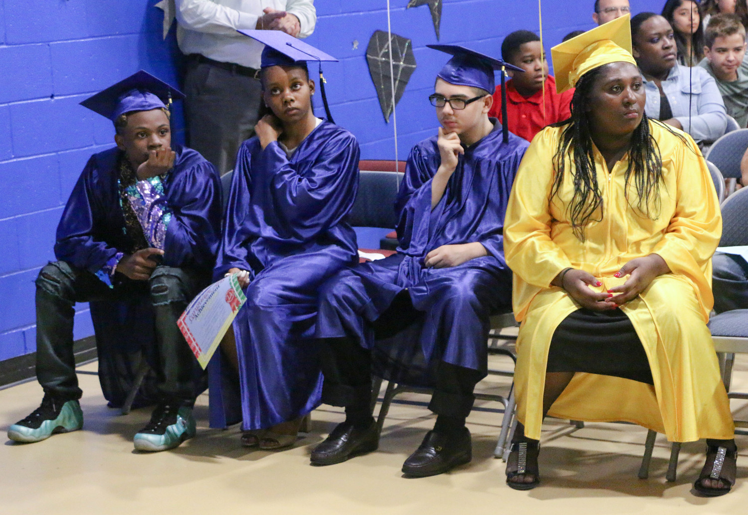 Graduates Shameak Bostick, left, Heaven Robinson, John Rouvelas, and Kristasia Bailey, right, waited for the end of the ceremony to turn their tassels and officially become high school graduates.