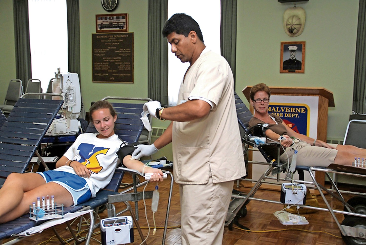 Blood Technician Chico Balram drew blood from Shannon O'Brien and Trish Montemarano during a blood drive at the Malverne firehouse in 2010.