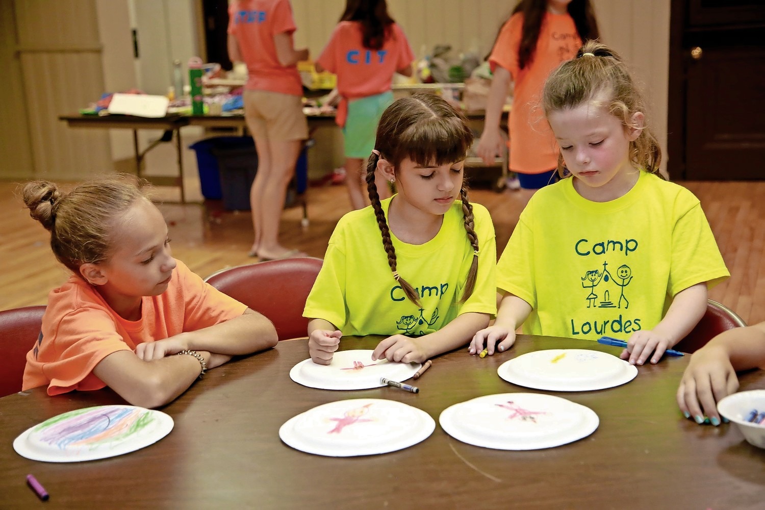 Ella Novack, left, watched as campers Natalie Ryder and Caitlin Egan work on their tambourines.