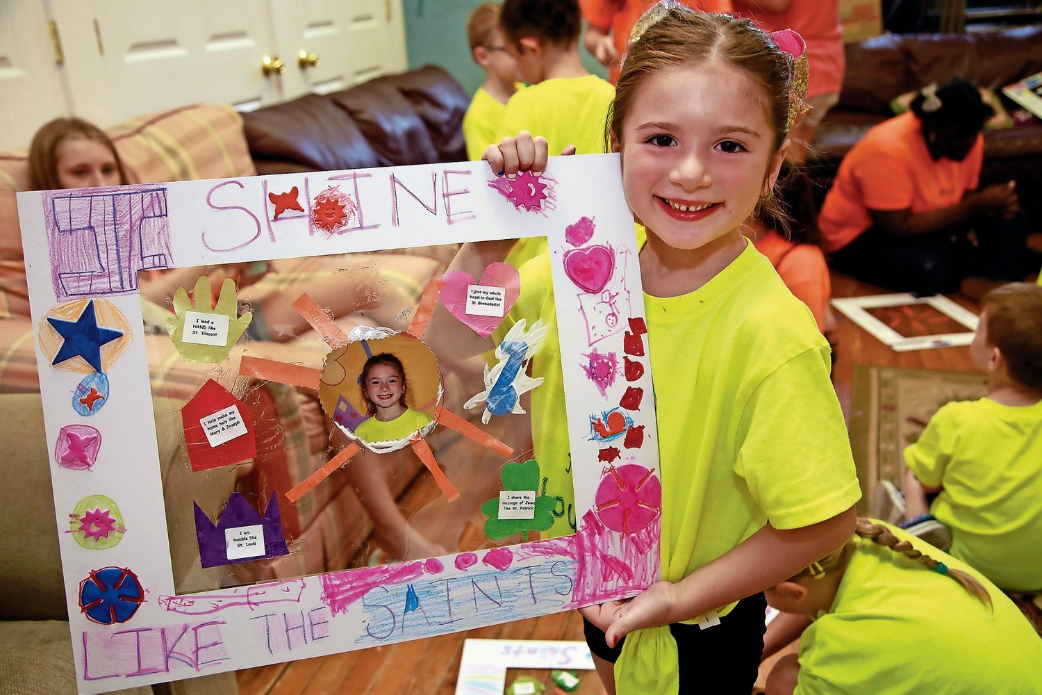 "Camper Madison Dauphin showed off her work, titled ""Shine Like the Saints,"" at Camp Lourdes' 20th anniversary celebration last week."
