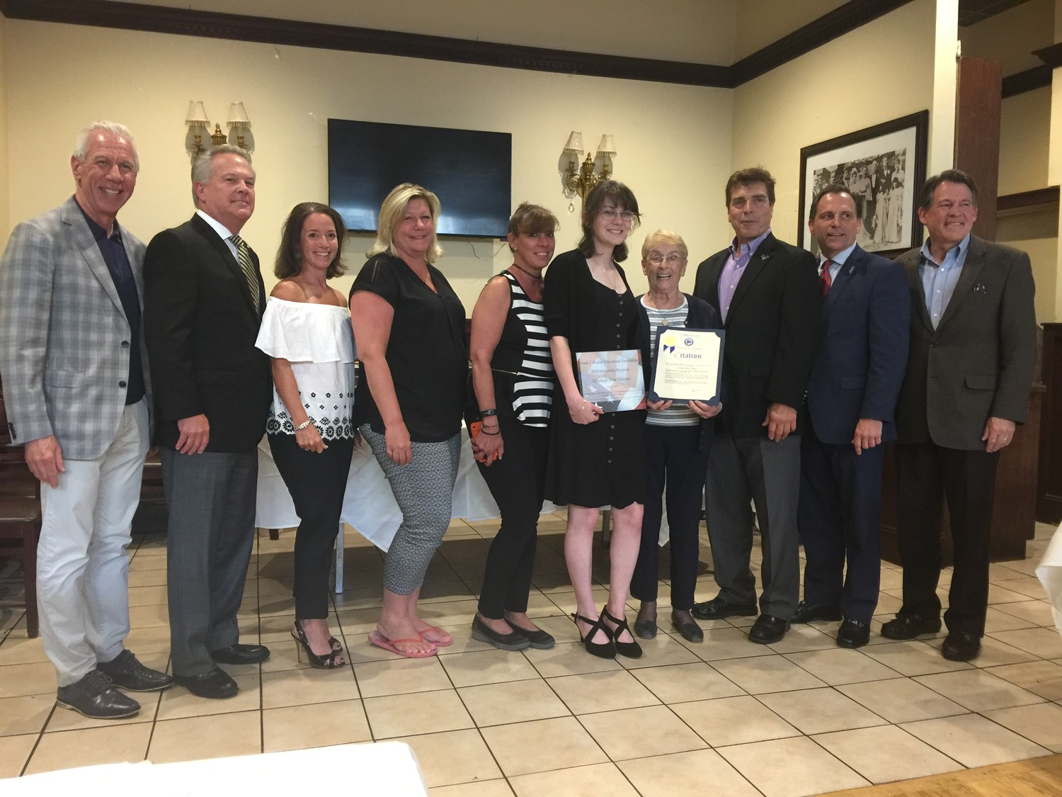 Elizabeth Johnson, fifth from right, was named the recipient of the annual Frank J. Becker Education Foundation Scholarship on June 28. Above, Johnson with Ken Jones, far left, Greg Becker, Karen Becker-Hynes, Lynbrook Village Trustee Ann Marie Reardon, Kathy Simon (Elizabeth's aunt), Lynbrook Mayor Alan Beach, Deputy Mayor Hilary Becker and Fran Becker.