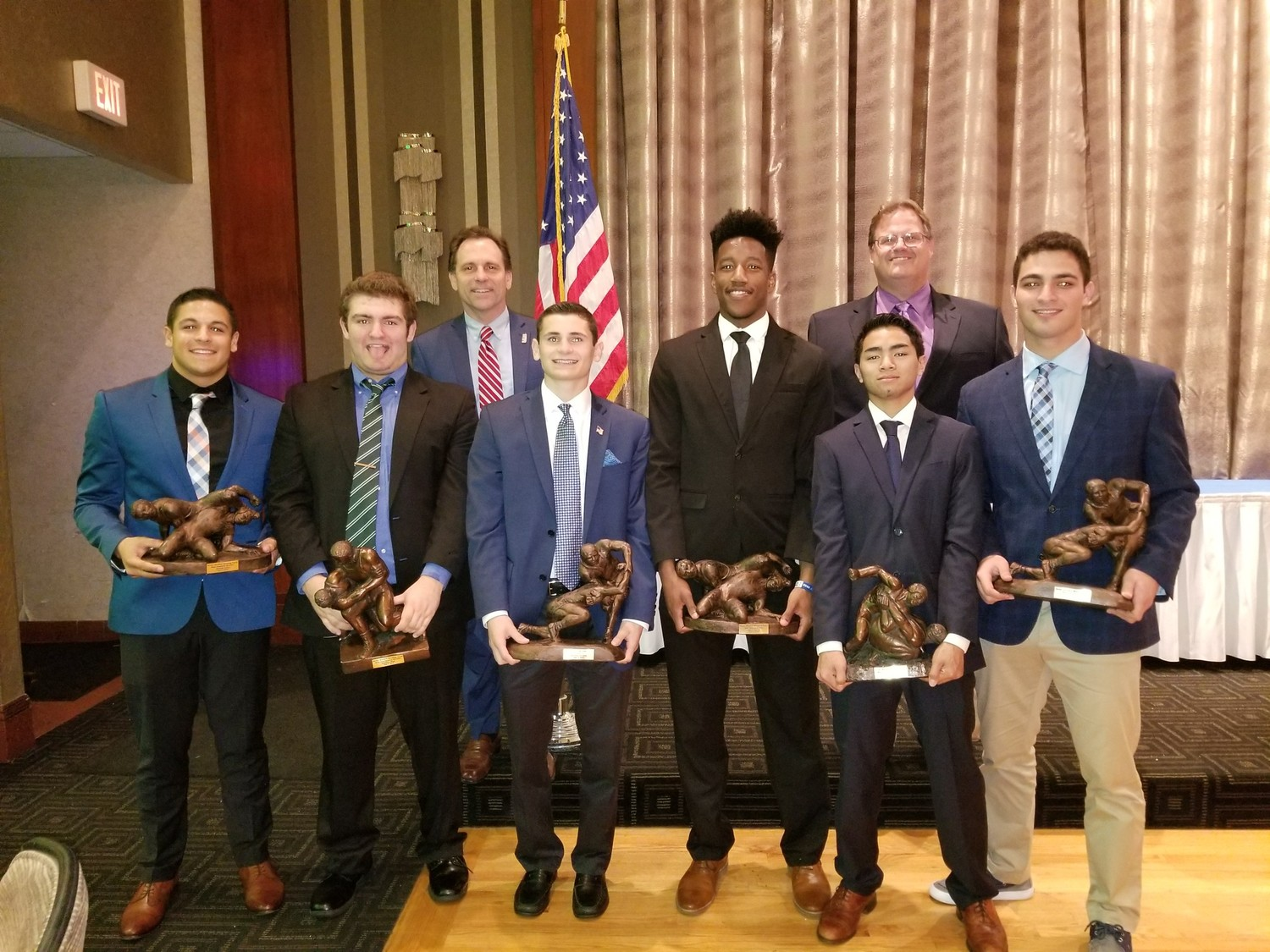 Lynbrook wrestlers Tom Urena, left, Matt Renz, Matt Ferrante, Justin Harvin, Joe Becker and Garrett Handel were honored at the annual Becker Brothers awards ceremony. Above, the wrestlers with Hilary Becker, head of the Lynbrook Titans Wresting program, back left, and varsity coach Richie Renz.
