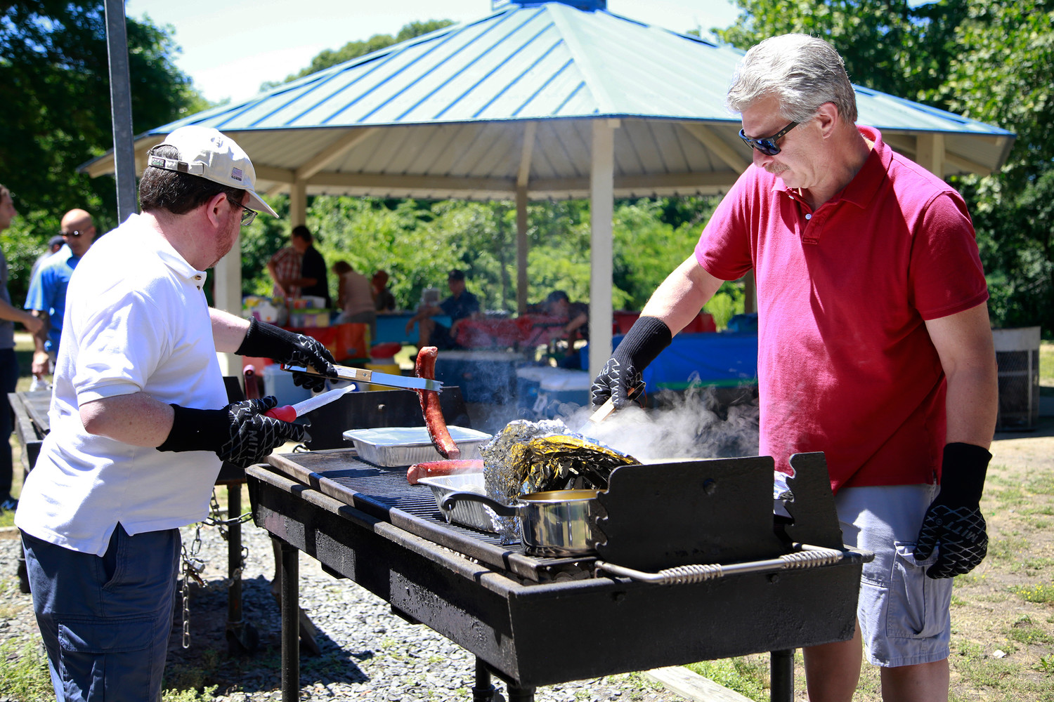 More than 100 people spent a hot summer day in Forest City Community Park in Wantagh, at the annual family picnic of the East Meadow Chamber of Commerce and Kiwanis clubs. To prepare for the feast, Eric Vogel flipped kielbasa while Jay Steinmetz tended to the clams.