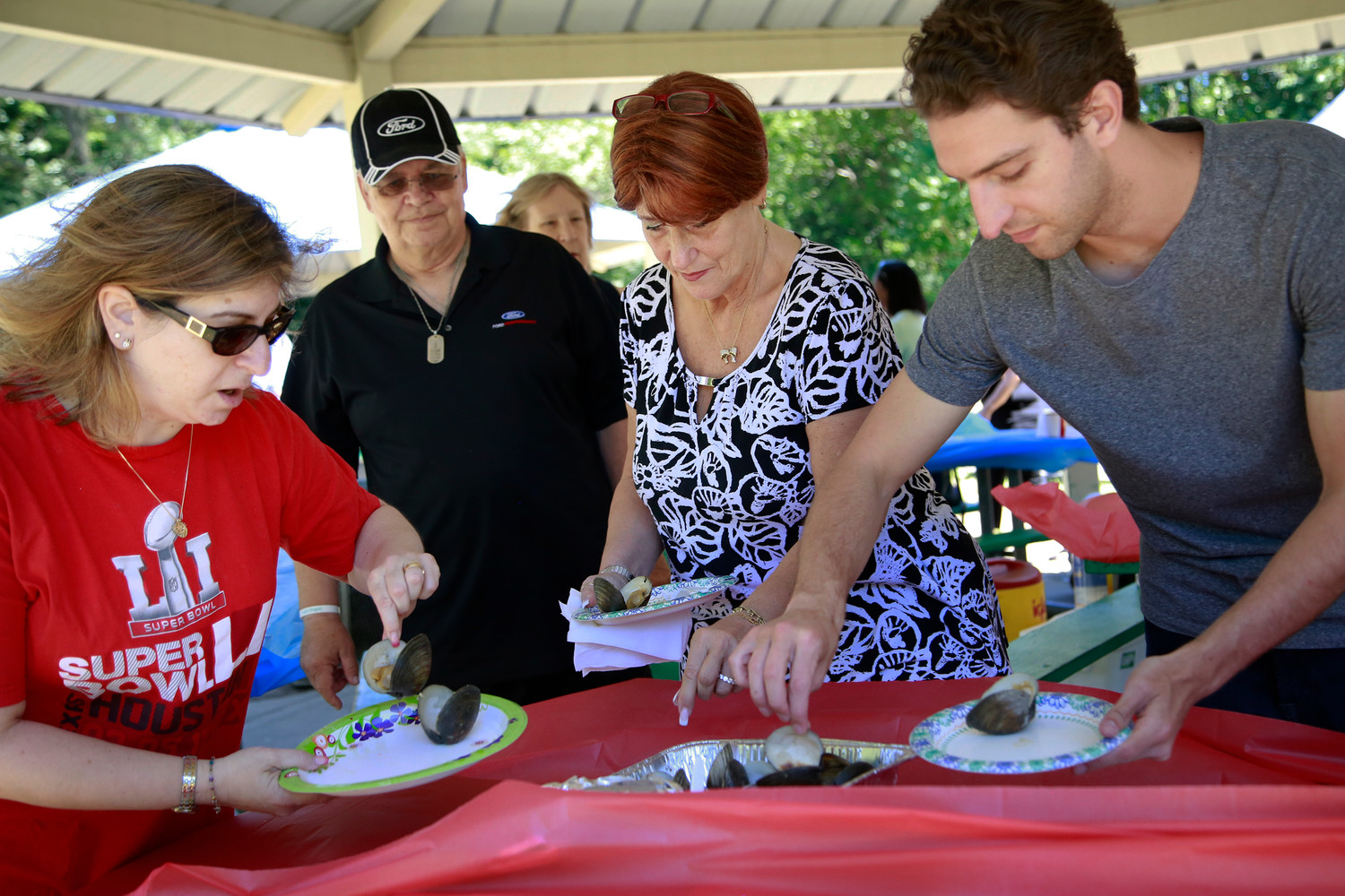 Gail Cummo, Ronni Fauci and David Perrotto, from left above, helped themselves to the steamed clams at the East Meadow Chamber of Commerce and Kiwanis clubs' annual family picnic.