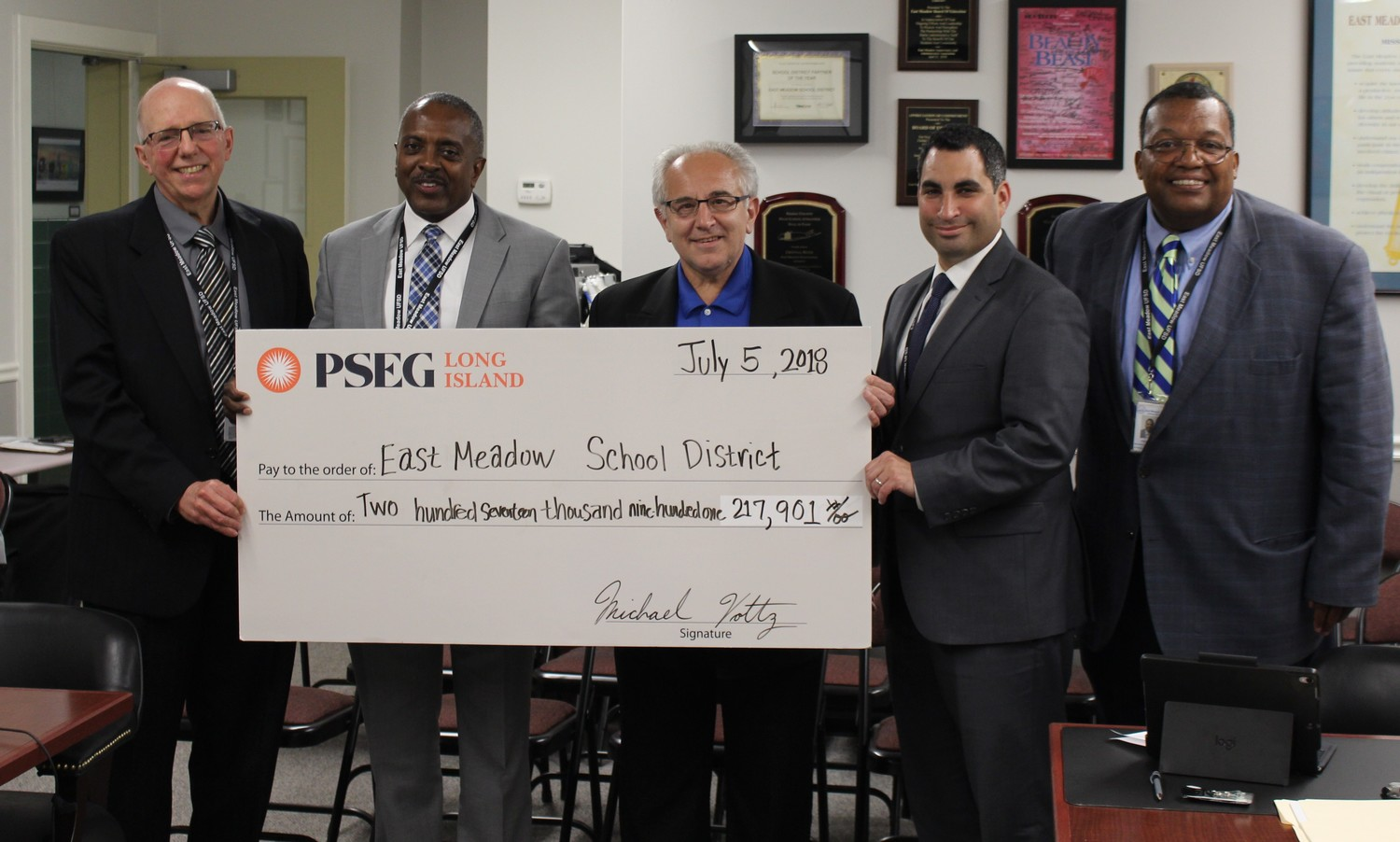 Domenic Abbatiello, center, a representative of PSEG Long Island, gave a rebate check to the East Meadow School District during a July 5 Board of Education meeting. Above is trustee Joseph Parisi, Superintendent Kenneth Card, President Matthew Melnick and Arthur Williams, the assistant to the superintendent for administration and special projects.