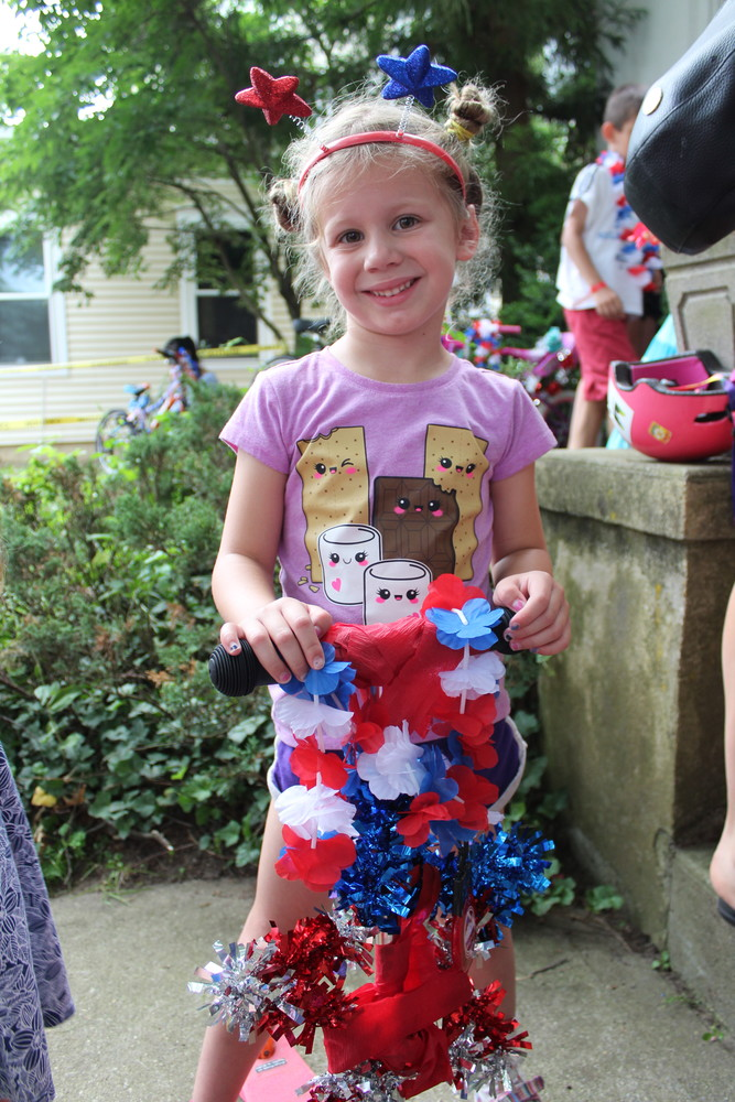 Amelia Kletter decorated her scooter with red, white, and blue leis before she decorated her head with a star headband.