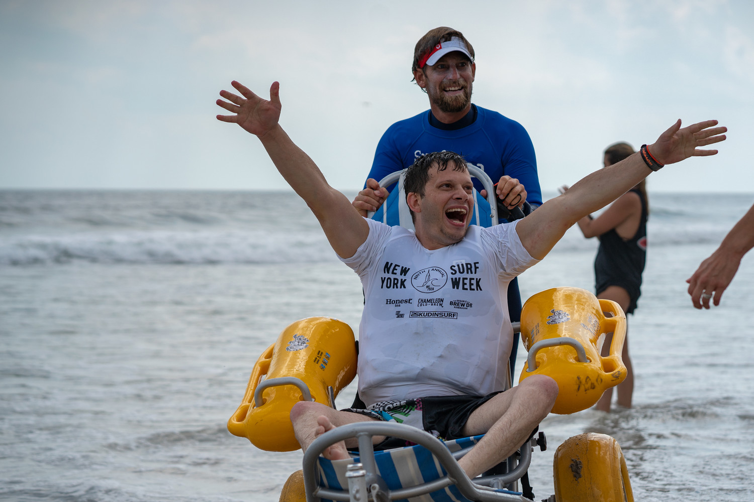 Professional big-wave surfer Will Skudin celebrated with Hofstra University professor and athlete Adam Halpern on July 12 at a surf outing for Surf for All, a local nonprofit organization that provides surfing opportunities for people with disabilities and special needs. The outing was part of the ninth annual NYSEA Surf Week, an event founded by Skudin.