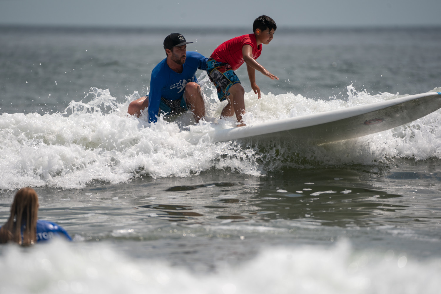 Volunteers assisted surfers with physical and developmental disabilities at the Surf for All outing.