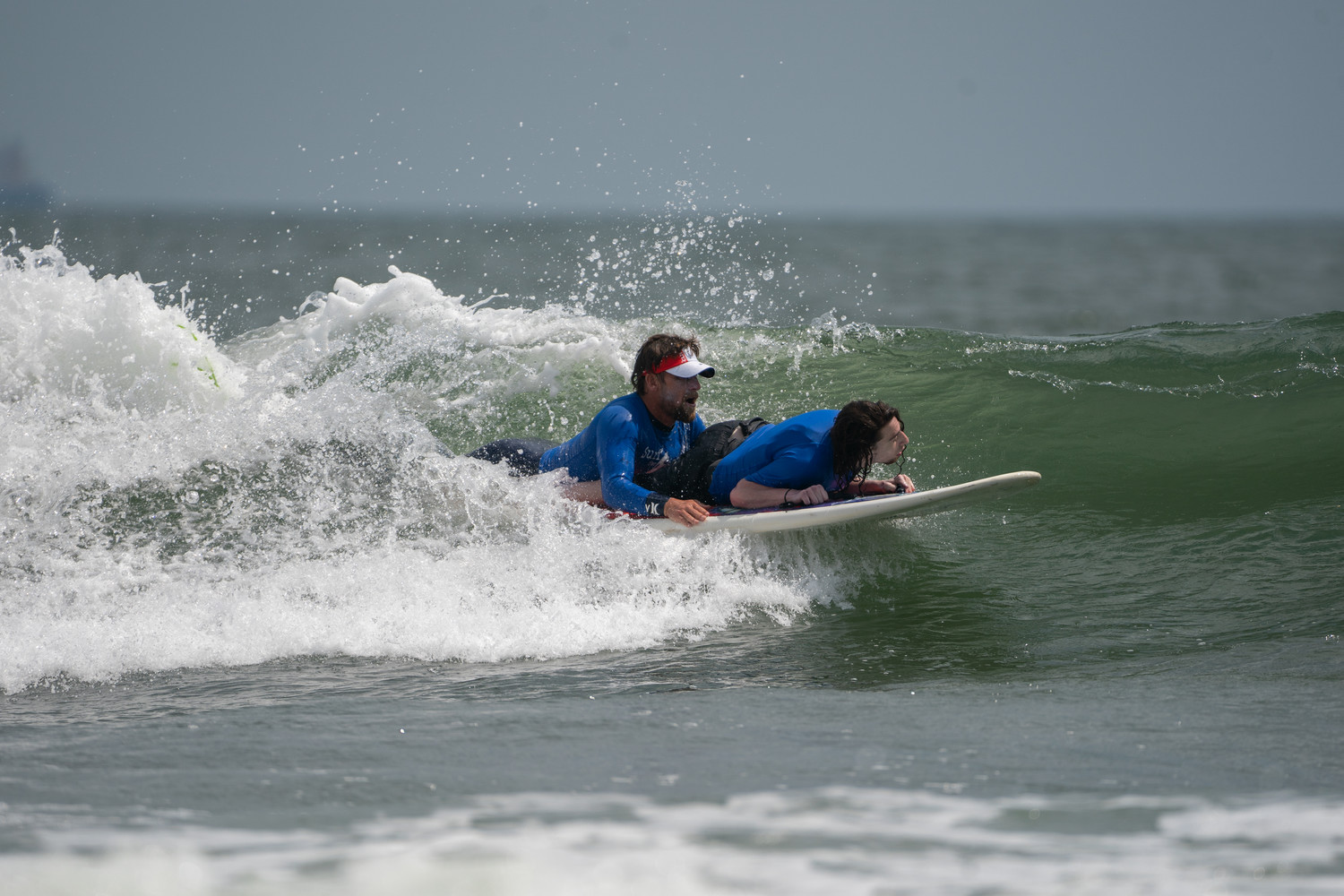 "Will assisted Dylan ""Surfing Samurai"" Hronec, a 26-year old who has cerebral palsy, at the Surf for All outing on July 12 at National Boulevard beach."
