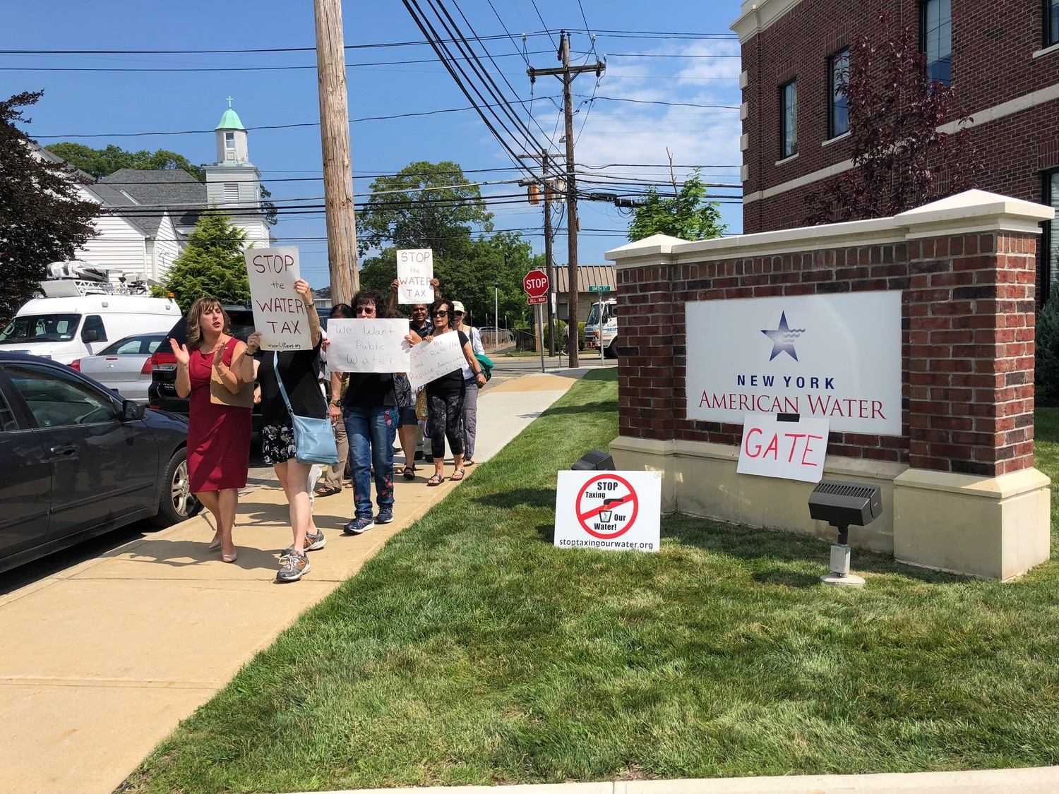 Assemblywoman Christine Pellegrino, far left, marched with protesters outside New York American Water's offices in Merrick on July 12, after announcing legislation to replace the company.