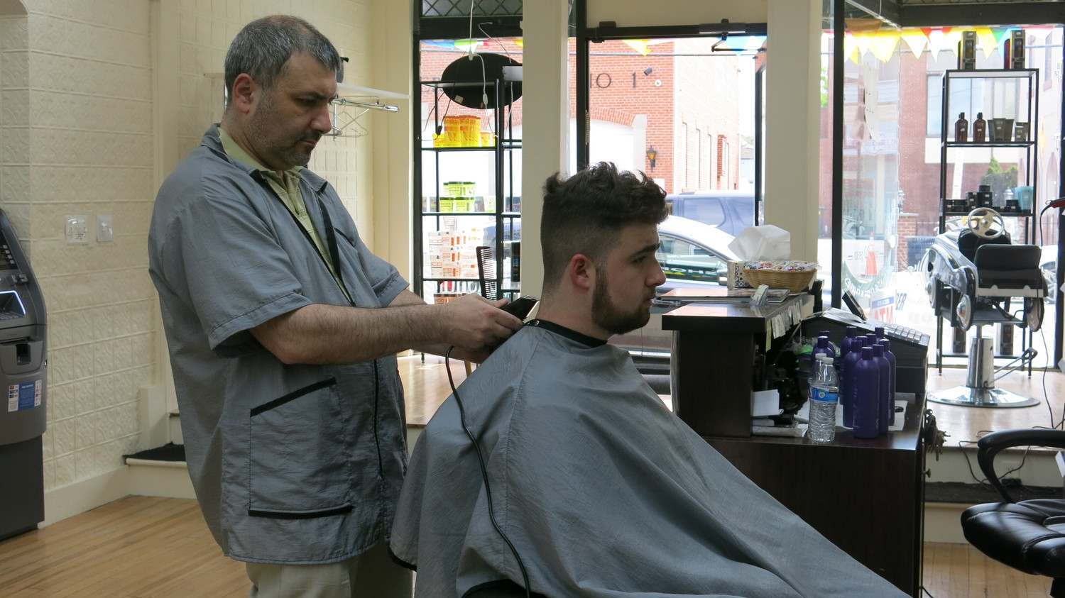 Alex Murdakhayev, the owner of Johnny's Barber Shop, worked to satisfy a new customer, Griffen Farrell.