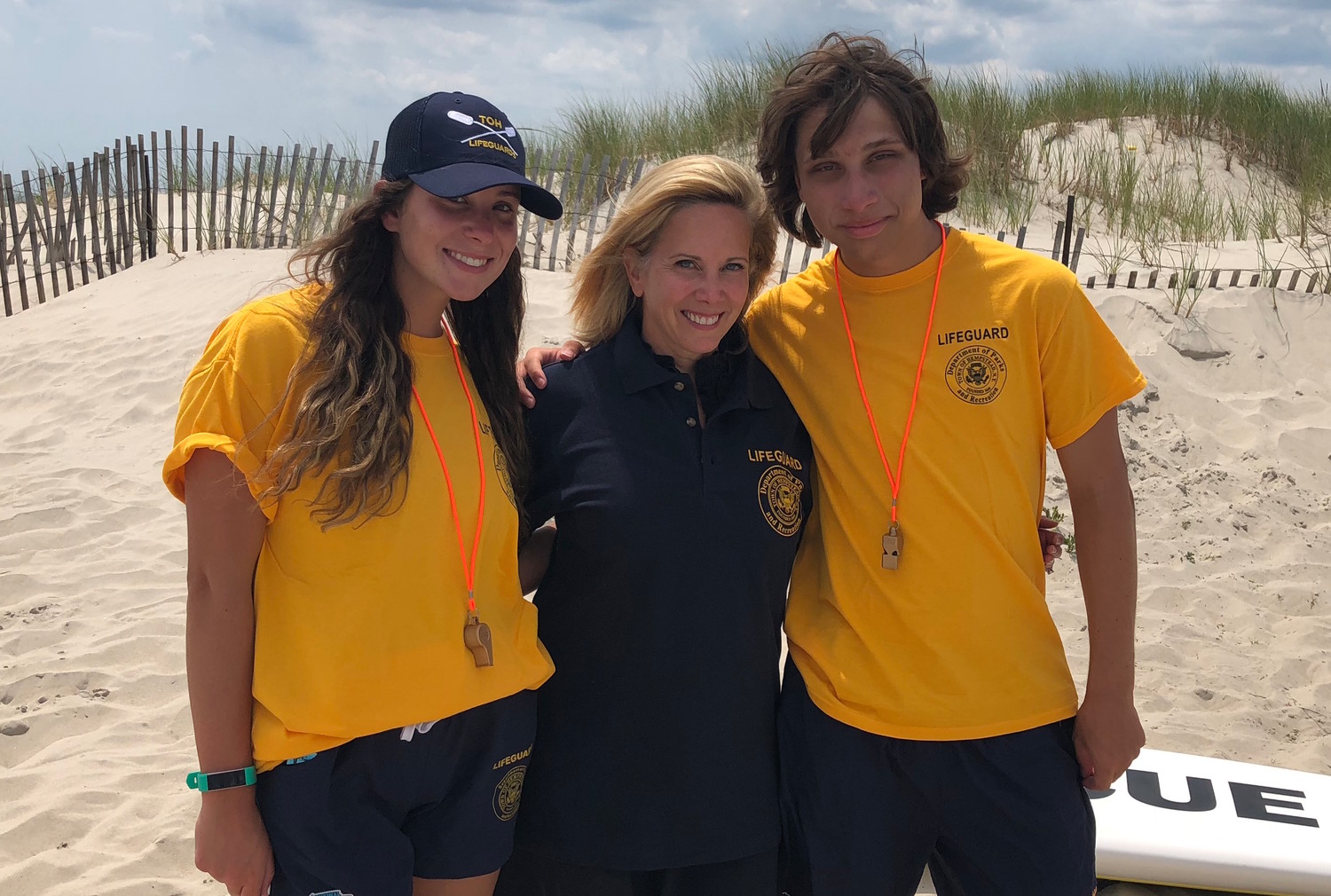 Lifeguard graduates Grace Hernon, left, and Connor Desmond with Town of Hempstead Supervisor Laura Gillen.