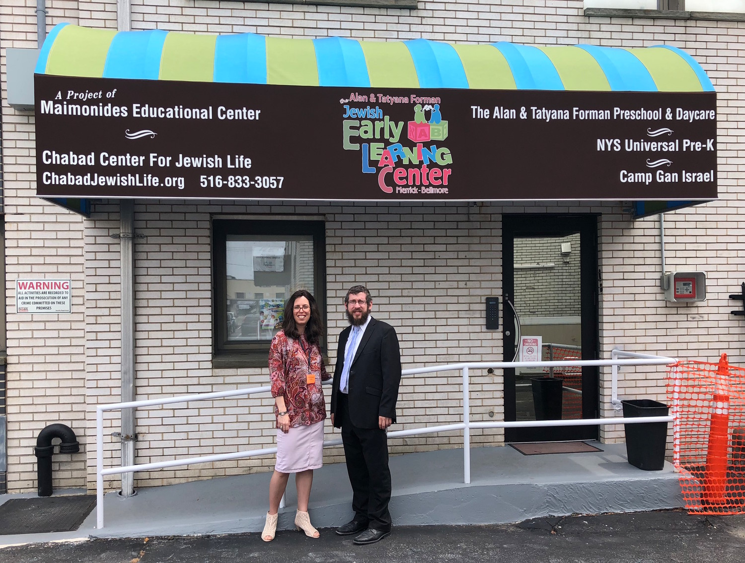 Rabbi Shimon Kramer and his wife, Chanie, under the new awning over the entrance to the Jewish Early Learning Center.