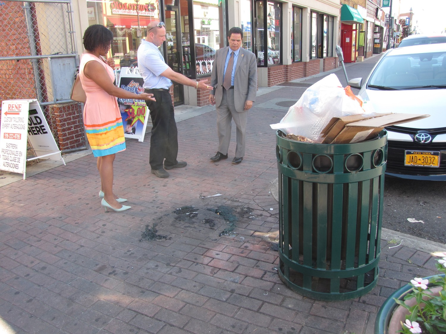 Jennifer Winters, vice president of the South Freeport Civic Association; Joseph Gambino, the group's president; and Cristobal Lopez, president of Latinos for Progress, checked out a trash receptacle in front of the Lopez Barbershop on South Main Street that overflowed with trash. The civic group and the Village of Freeport are teaming up to clean up South Main.