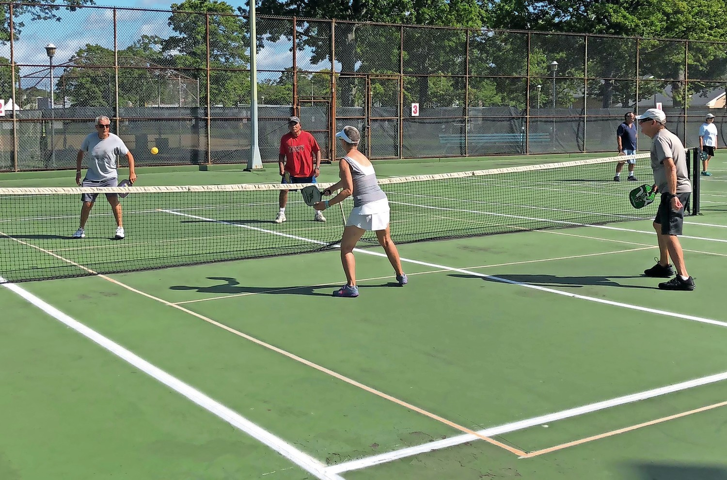 Pickleball players make use of the entirety of the Merrick tennis courts when they play seven mornings a week.