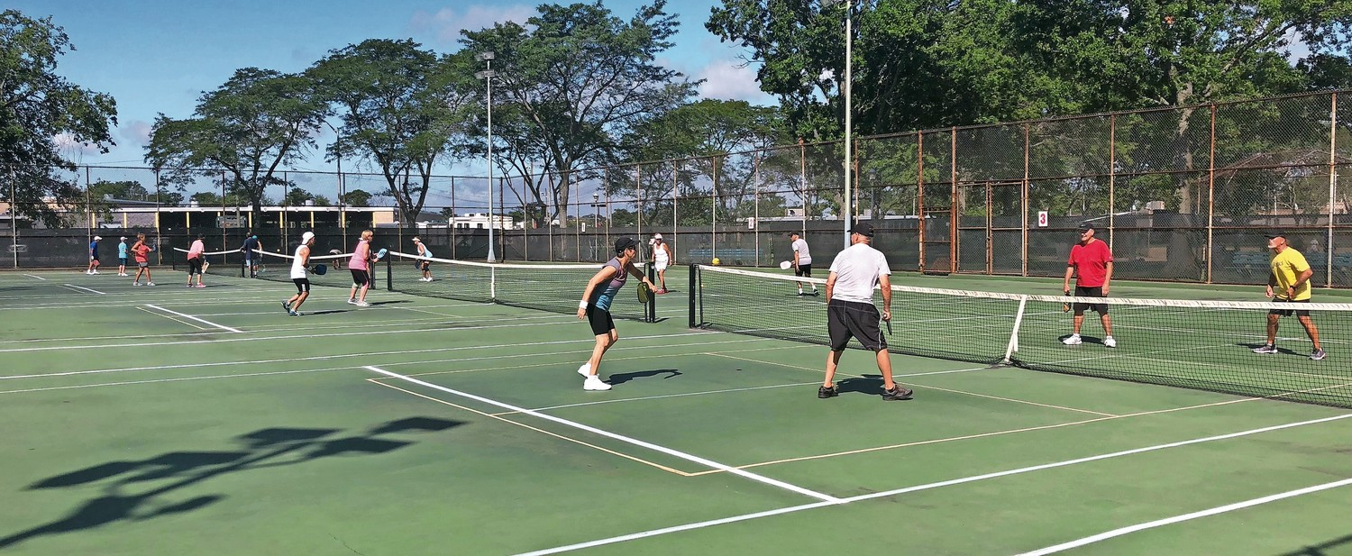 Pickleball players around Long Island play on re-purposed tennis courts. The temporary taped lines are orange.