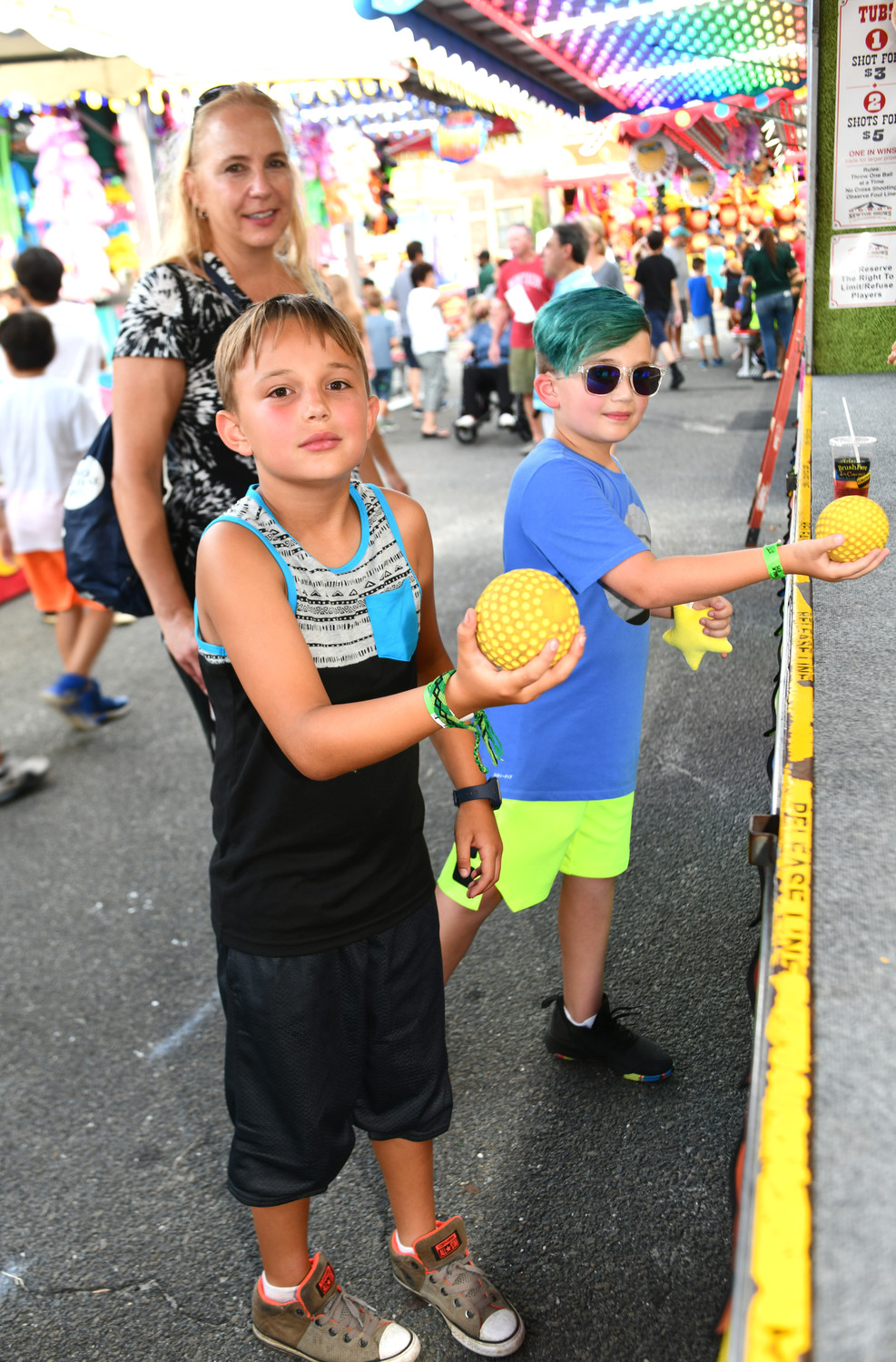 Logan Calamusa and Jacob Adoni tried their luck at a carnival game, supervised by Logan's mother, Katia.