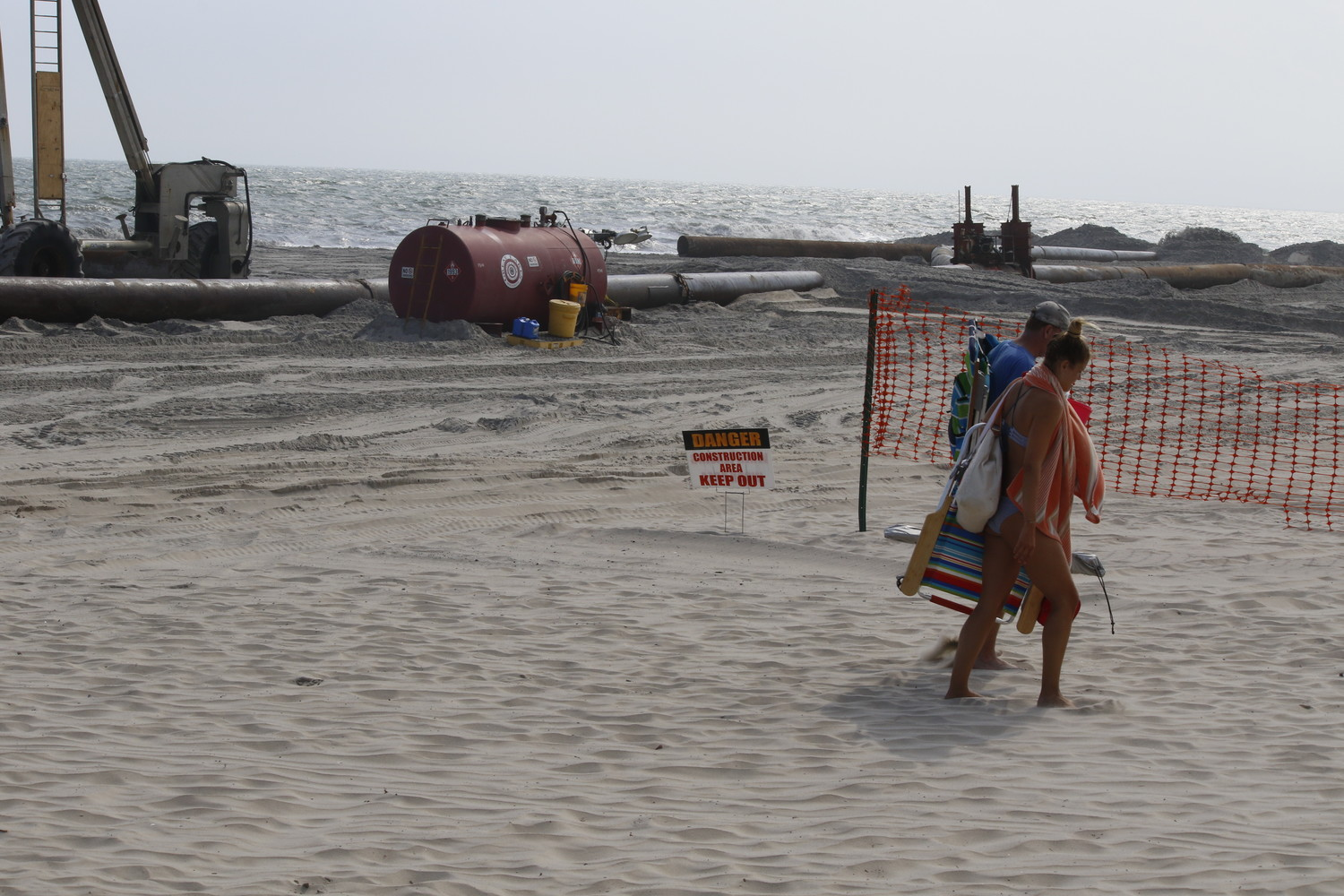 Amid a heat wave, beachgoers walked to an open beach on Tuesday along a path next to the work site where the Army Corps of Engineers is replenishing sand.