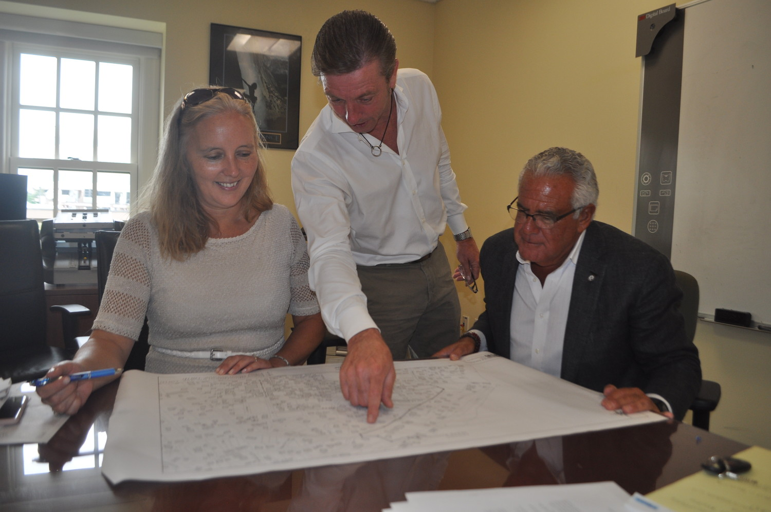 County Legislator Delia DeRiggi-Whitton reviewed plans for the new gravity sewer line with Sea Cliff Village Administrator Bruce Kennedy, center, and Mayor Edward Lieberman on July 30.