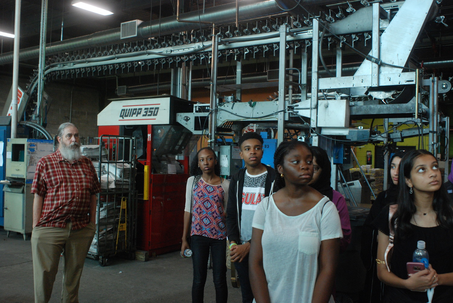 Institute participants toured Herald Community Newspapers in Garden City, including the pressroom. They were joined by, at left, Timothy Denton, editor of the Franklin Square-Elmont and Valley Stream Heralds.