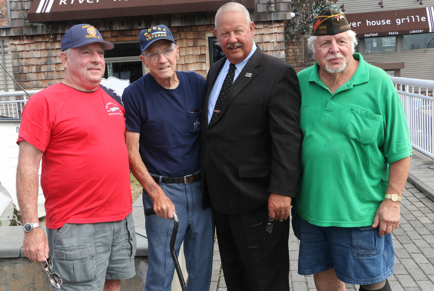 A number of veterans, Ed Martin, left, John Remsen, along with Mayor Robert Kennedy, also a Navy veteran, and Vinnie Mientus, right, attended the welcoming of the U.S. Naval Academy midshipmen.