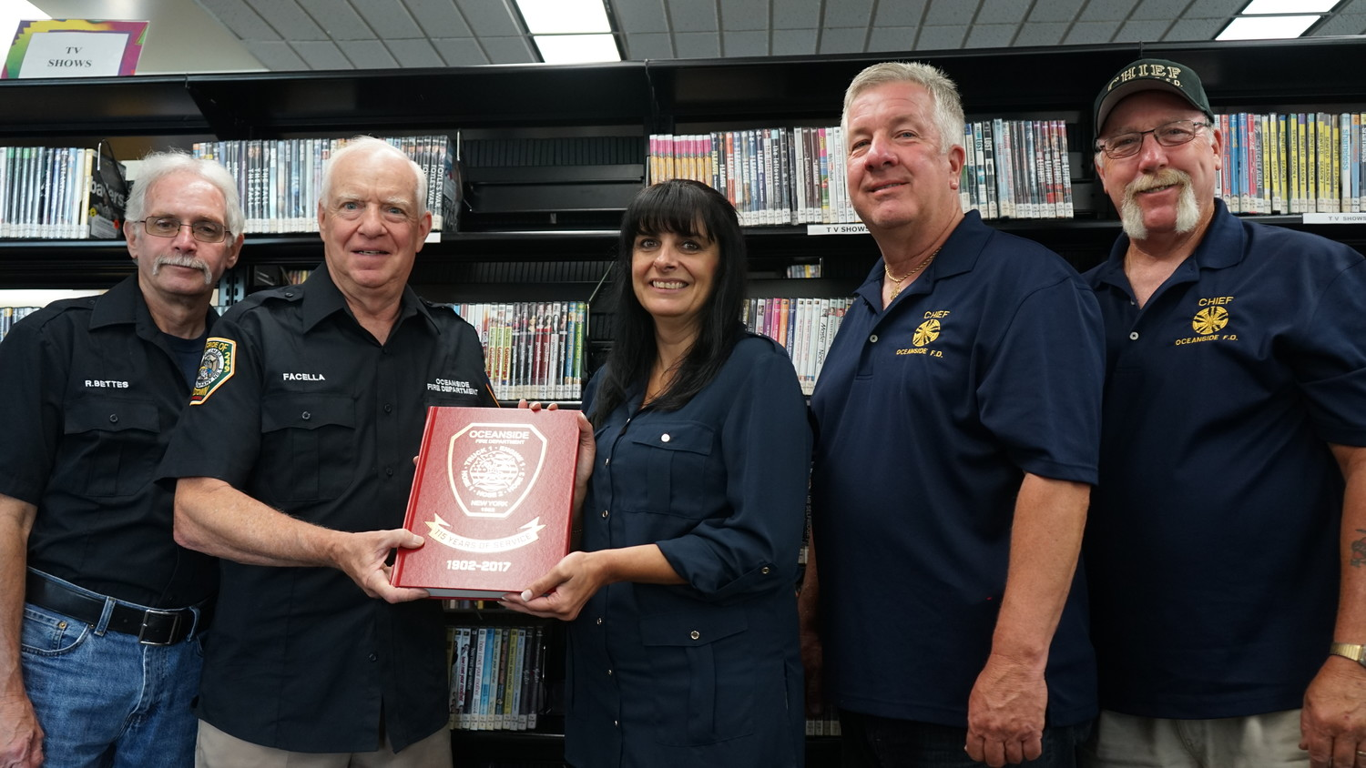 Oceanside firefighters Bob Bettes, left, Paul Facella, Bill Lynch, Fred Robinson and Oceanside Library Director Chris Marra with a copy of their history of the Oceanside Fire Department donated to the library for future generations of Oceanside history lovers to enjoy.