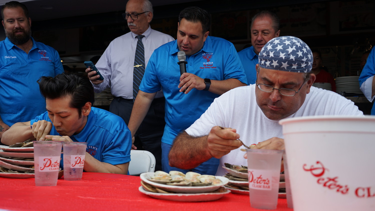 "Celebrity competitive eaters Takeru Kobayashi, left and Ed ""Cookie"" Jarvis demonstrated their clam-eating prowess before the competition with former IPFD Chief Anthony D'Esposito on the mic."