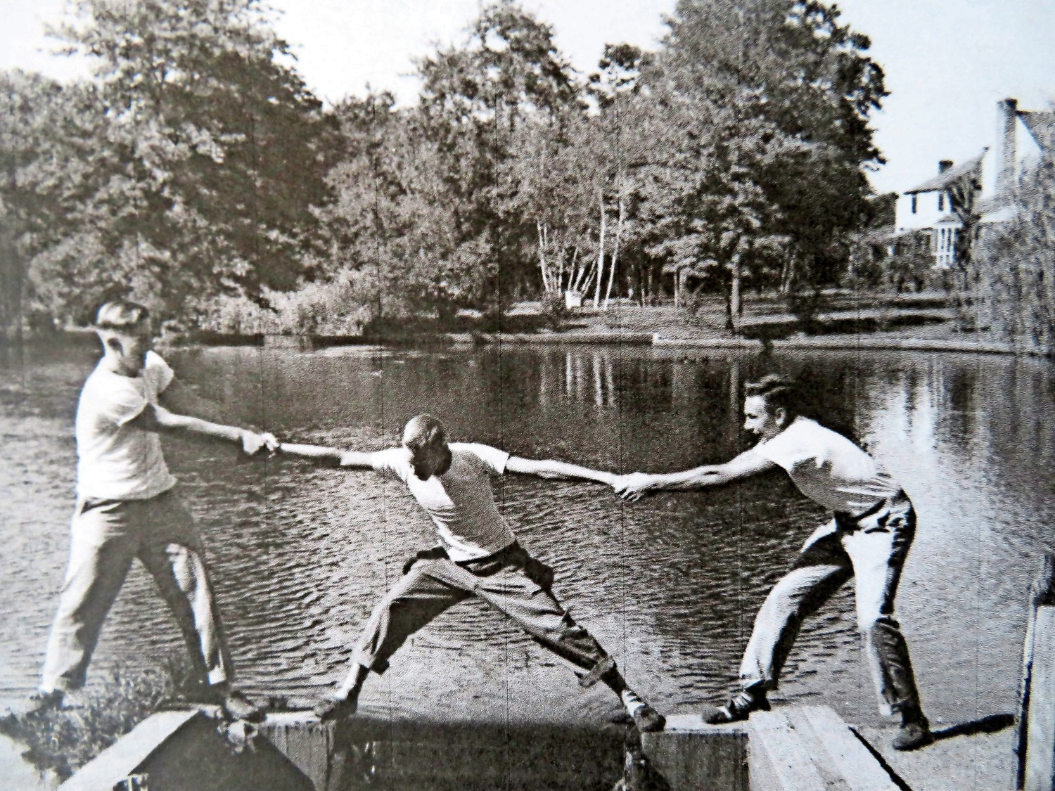 Three young men doing high jinks at Collin's Pond in the 1940s.