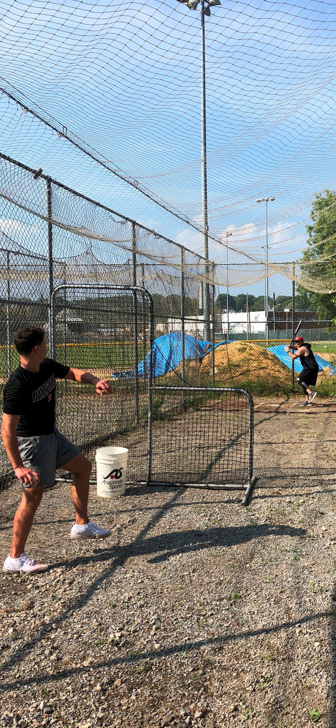 Michael Damiano, pitching, used the batting cages to train for LIU Post baseball team tryouts this fall. Jonathan Capobianco, batting, helped him practice.
