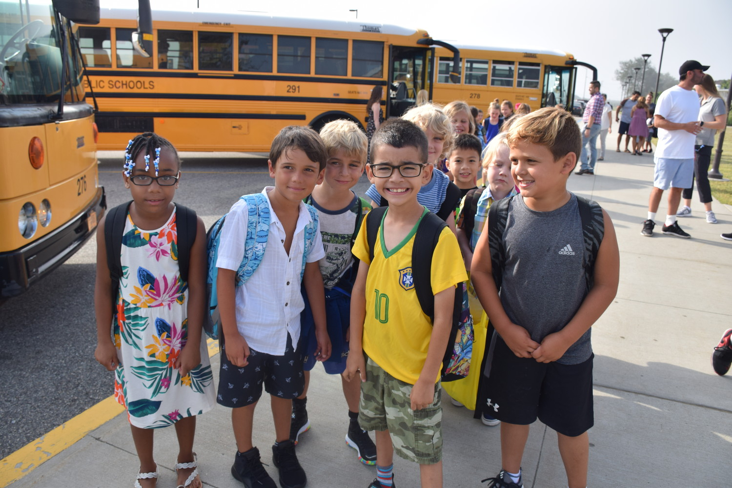 Lido Elementary School students stepped off buses and waved off their parents as they went back to school on Wednesday. At right,