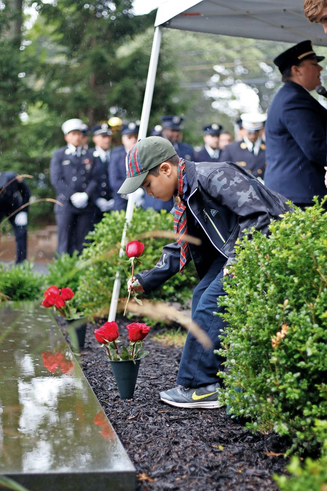 As names were read a rose was placed at the memorial by cub scouts from pack 240. Logan Shinsato, 9, placed his rose.