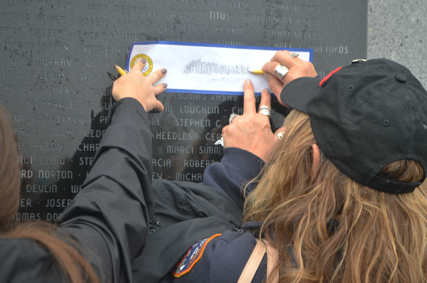 Bethpage resident Toni Ioveno made an impression of the name of her late friend, Charles Noran, etched on the Town of Hempstead's memorial wall in Point Lookout.