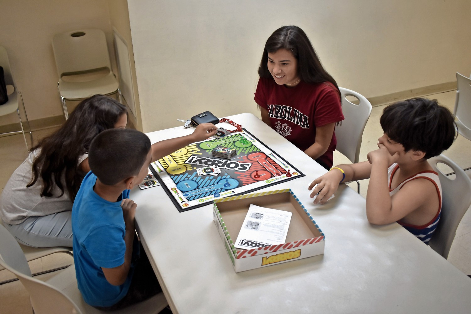 Tutor Molly Farina, clockwise from top, 17, played a board game with Leo Almonte-Baez, 8, Erik Duran, 6, and Ciara Borrero, 11.