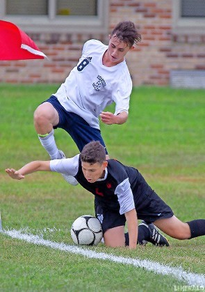 Oceanside's Austin Ortiz, No. 8, tried to gain possession from Syosset's Matthew Leav during last Friday's 1-1 draw in the Conference AA-1 opener.