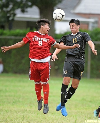 Freeport's Sebastion Arboleda, left, and Uniondale's Walter Gomez went airborne during last Friday's opener won by the Red Devils, 2-0.