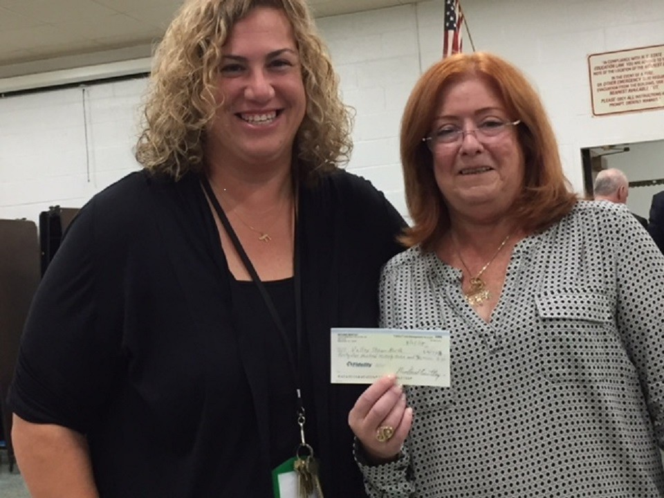 Sheila Brayman Borgese, right, presented North High School Principal Rachel Green with a check for security improvements at the Board of Education meeting on Sept. 4.