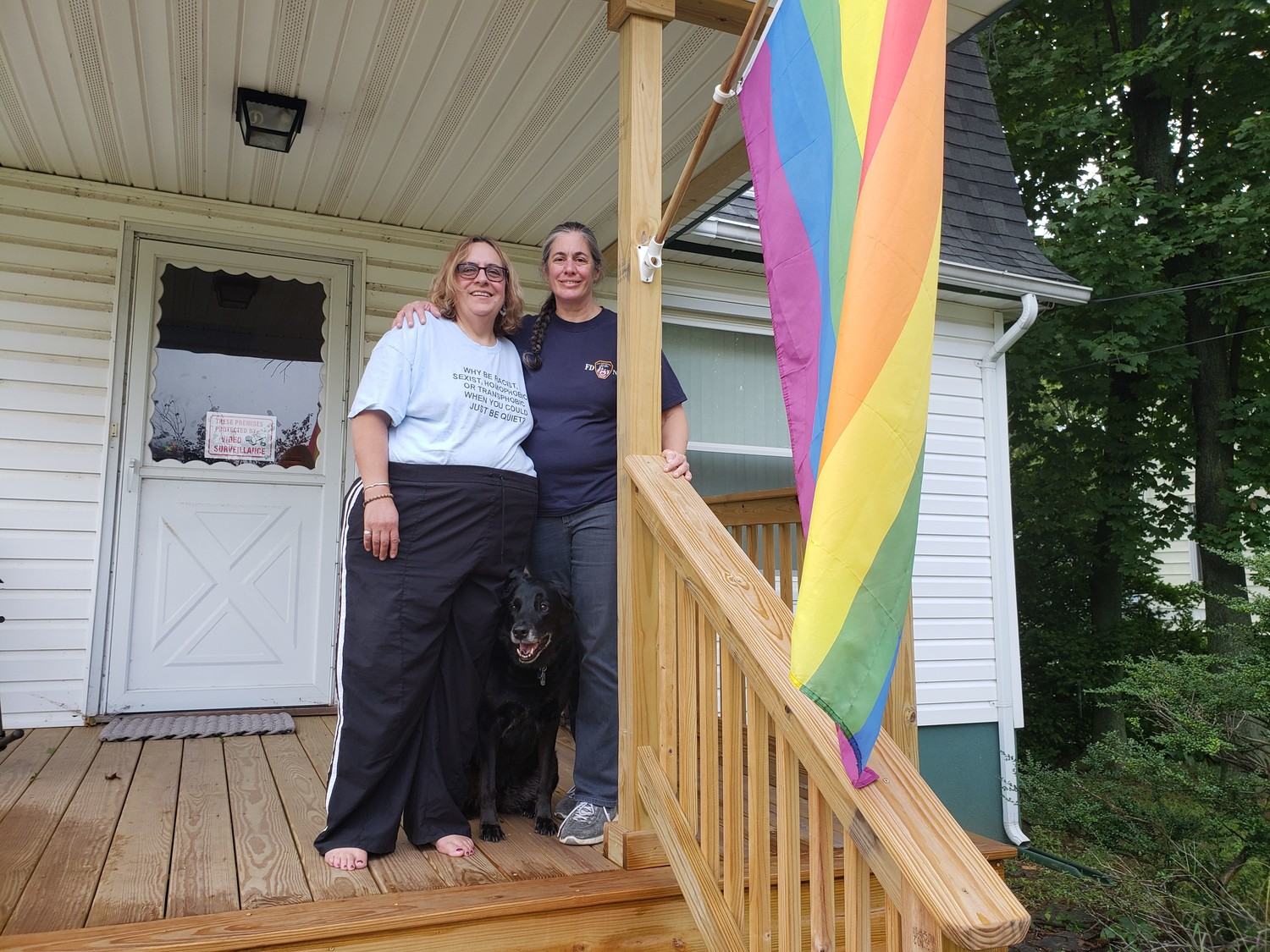 Celia Fabrizio, left, and Patricia Chiapuzzi were all smiles in front of their new rainbow flag with their dog Jet on Sept. 11, but they weren't smiling last month when their previous flag was taken down by a vandal. The two married in September 2013, shortly after a Supreme Court decision allowed same-sex couples to wed.