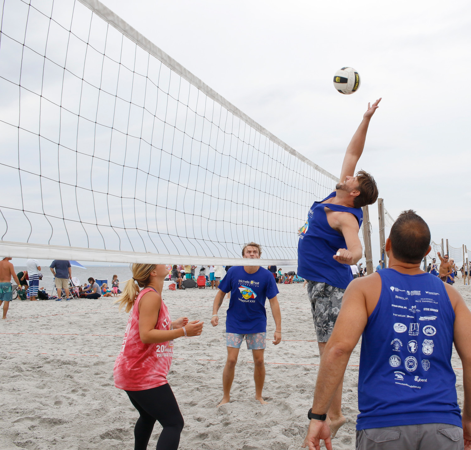 David Sorise spiked the ball over the net as his team, Socks on the Beach, competed against the Fozzies at the 22nd annual Michelle O'Neill Volleyball Tournament on Sept. 8.