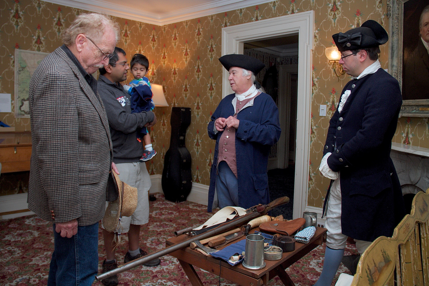 Charles Monette, far left, and Niten Jaiswal and his 18-month-old son, Rian, learned about colonial militia gear from Robert Ambrose and Patrick Mantle, members of the Huntington Militia.