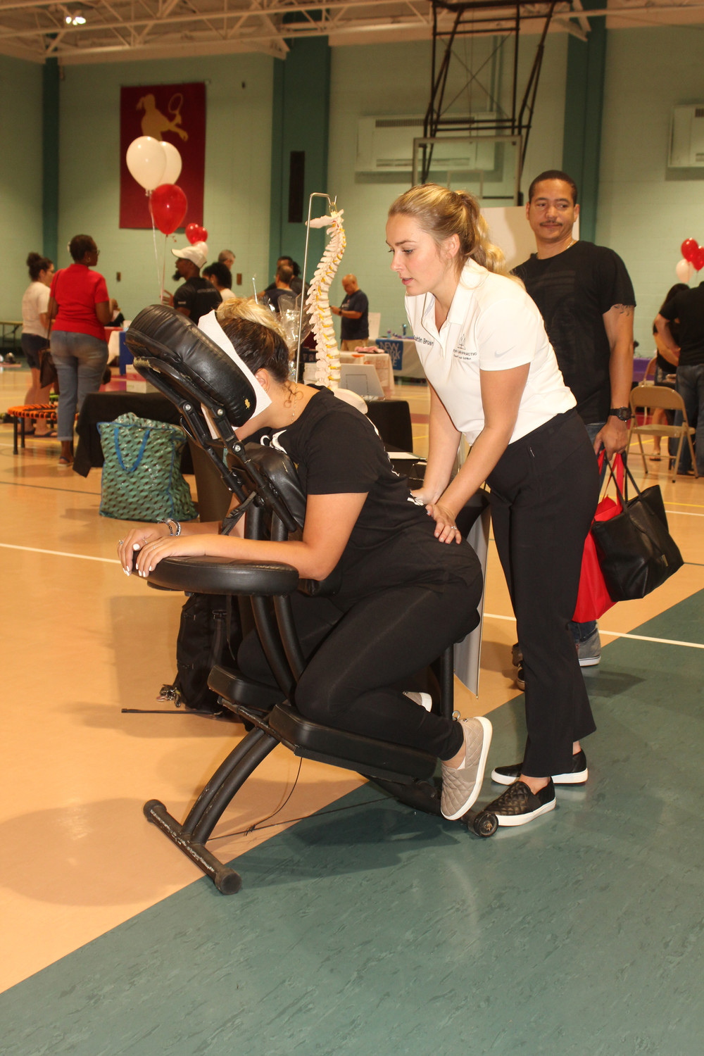 Dr. Caitlin C. Brown from Brown Chiropractic in Lynbrook helped an attendee release tension on her lower back during the health and wellness event.