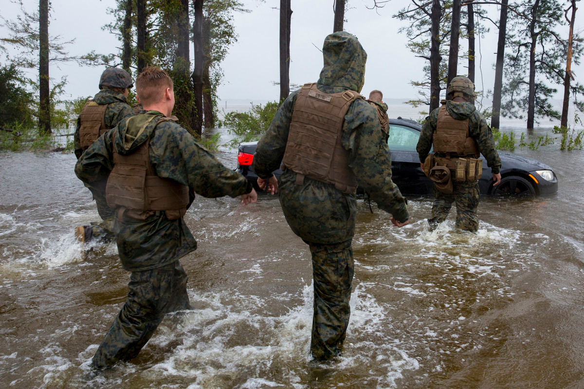 Marines ran to help push a car out of floodwaters at Marine Corps Base Camp Lejeune.