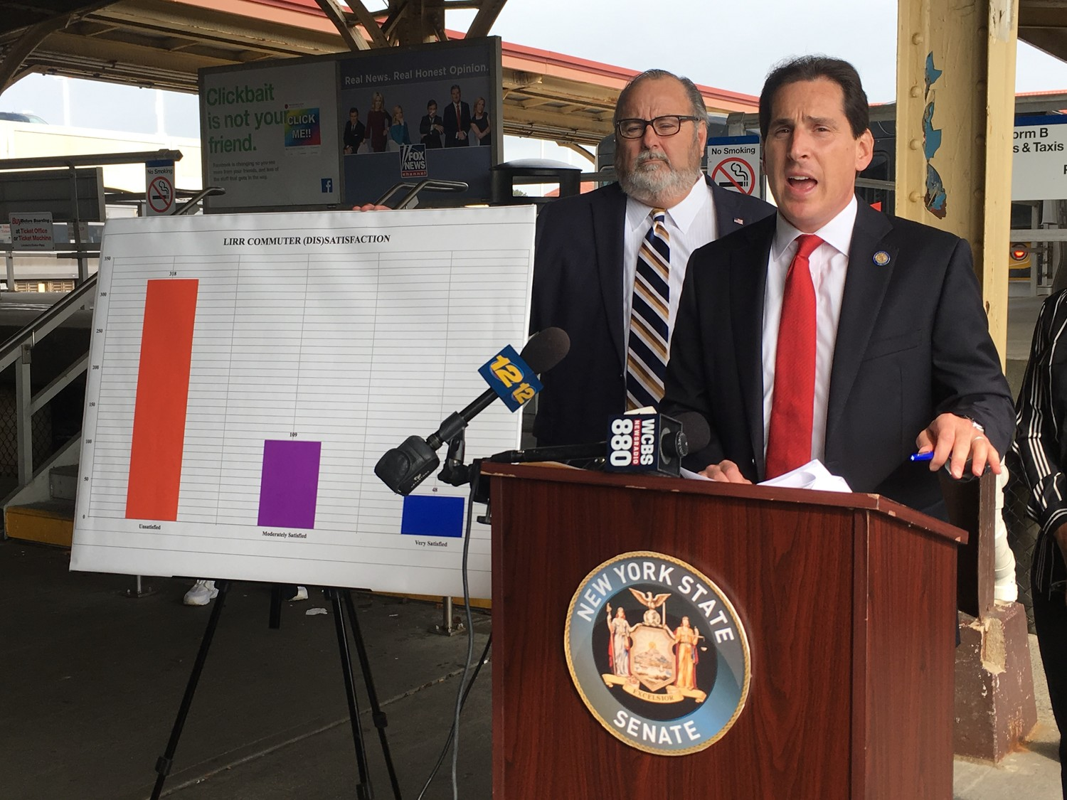 State Sen. Todd Kaminsky, at lectern, announced the results of a MTA Long Island Rail Road commuter survey at a news conference at the LIRR station in Long Beach on Sept 18. Rockville Centre Mayor Francis X. Murray was among those who joined him.