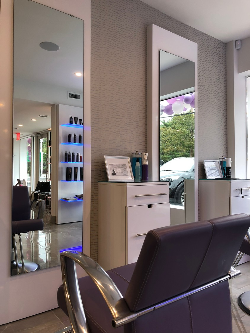 The salon is open and inviting, with gray marble floors and accents of soft purple and silver.