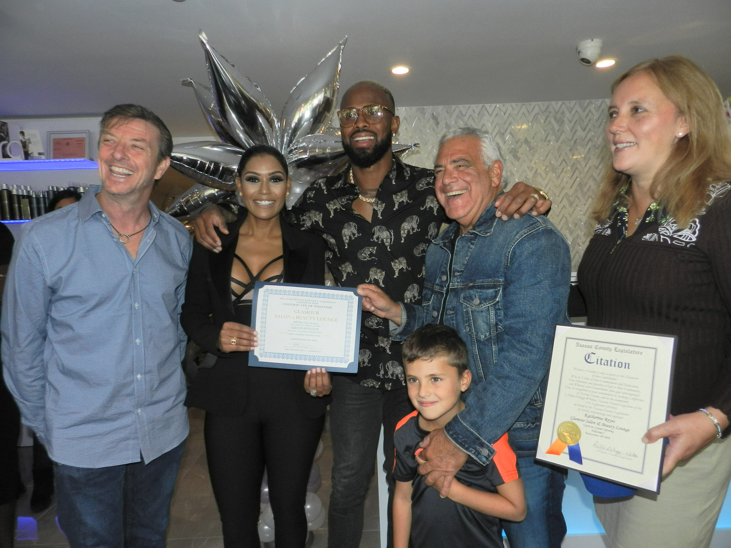 Village Administrator Bruce Kennedy, far left, Katherine and Jose Reyes, Mayor Edward Lieberman, his grandson Cole, and County Legislator Delia DeRiggi-Whitton got acquainted at the grand opening of Katherine Reyes's salon, Glamour, on Monday.