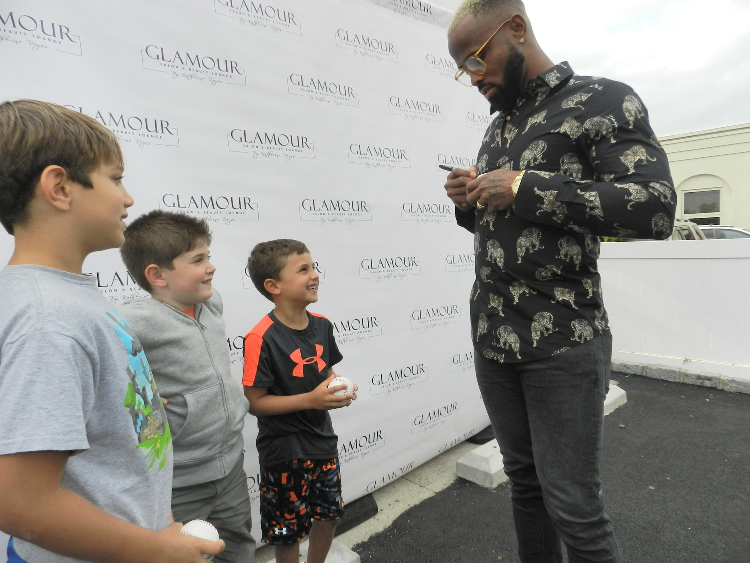 New York Mets shortstop Jose Reyes signed baseballs for fans Christopher Capogna, far left, Dean Stanco and Cole Bertinetti at the grand opening of his wife Katherine's new business, Glamour Salon & Beauty Lounge.