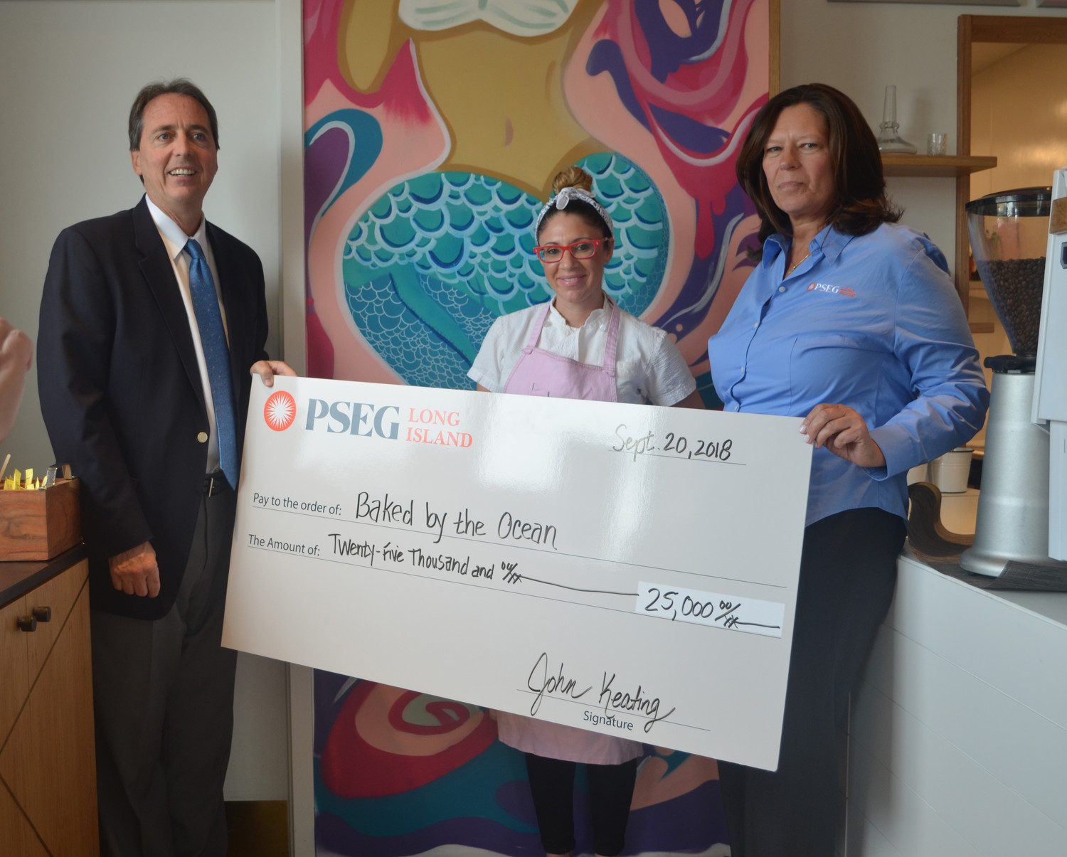 John Keating, manager of economic development for PSEG Long Island, left, and Linda Herman, economic development specialist at PSEG, far right, presented Baked by the Ocean owner Catherine Schimenti with a $25,000 check for building her business with energy efficient equipment.