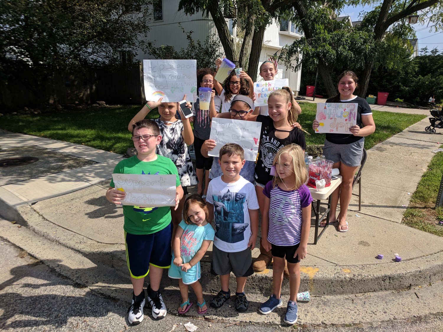 A dozen children, with the help of adults, set up a lemonade stand in Island Park to raise money for flood victims in North Carolina in the aftermath of Hurricane Florence.