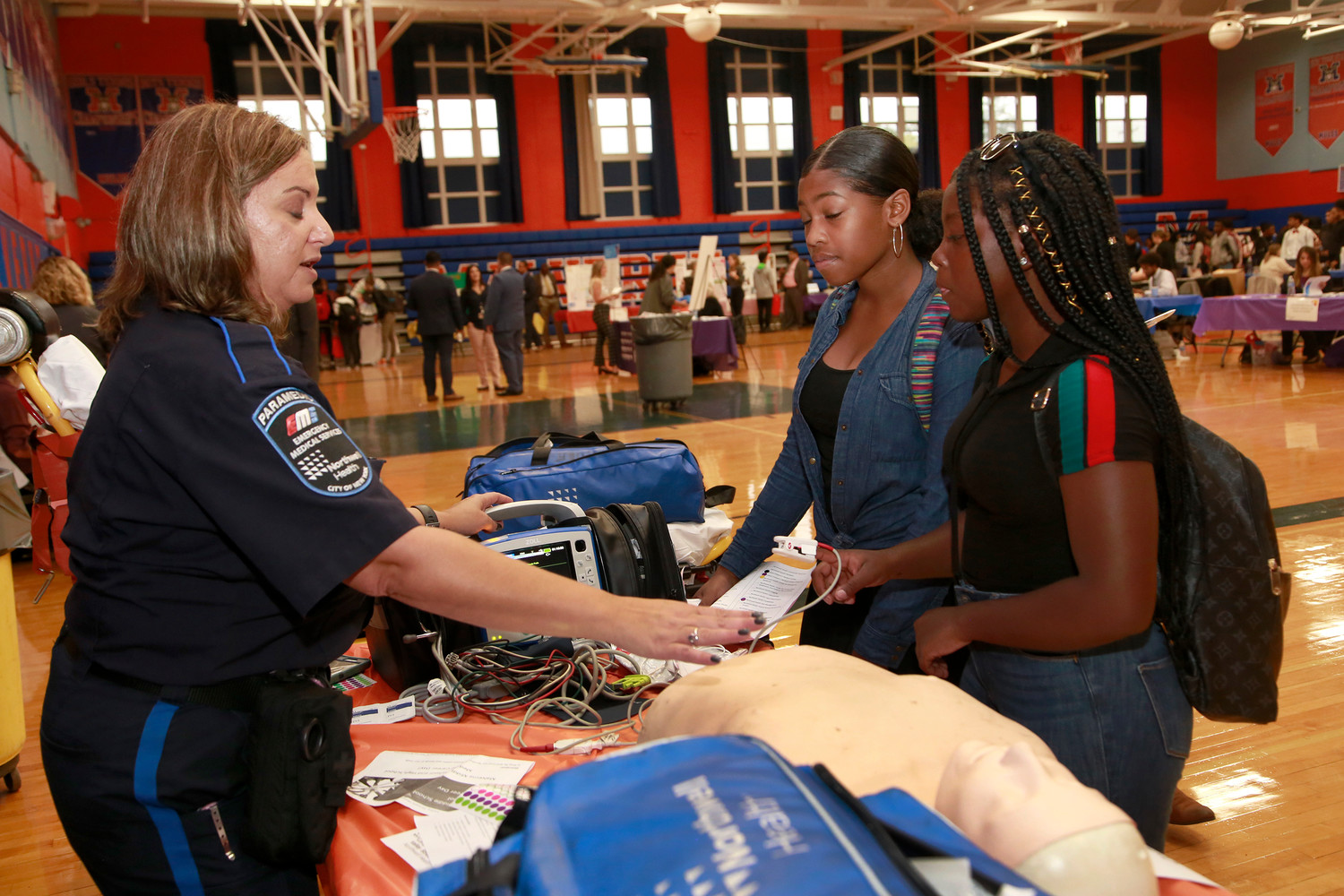 Freshmen Aniyah Smith, center, and Jazmyne Ackies learned some of the basics of CPR with an EMS worker from Northwell Health.